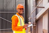 picture of transformer  - male african electrical worker in front of transformer - JPG