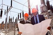 image of substation  - power company managers discussing blueprint at electrical substation  - JPG