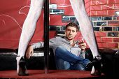 stock photo of stripper shoes  - The man observes dance round a pole - JPG