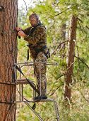 stock photo of harness  - Bow hunter in a ladder style tree stand correctly attaching a fall arrest harness to a strap around the tree - JPG