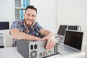picture of beside  - Computer engineer smiling at camera beside open console in his office - JPG