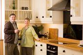 Senior Couple Portrait In Modern Designer Kitchen