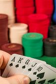 pic of flush  - Photo of a person holding a royal flush in front of stacks of gambling chips - JPG