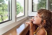 picture of cute little girl  - pretty smiling little girl on balcony look from window - JPG