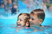 image of swimming pool family  - Smiling boy and little girl swimming in pool in aquapark - JPG