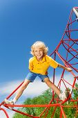 image of legs apart  - Active boy stands on red rope with legs apart and holds rope with one arm - JPG