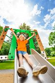 picture of chute  - Boy sliding on metallic chute with hands up - JPG