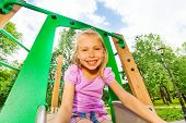 stock photo of chute  - Portrait of funny smiling small girl on playground chute looking straight - JPG