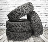 pic of four-wheel drive  - Stack of four new black tyres for winter car on  wooden floor in vintage room with brick wall background - JPG
