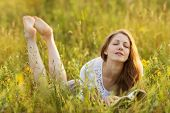 picture of beatitudes  - Happy girl with a book in the grass dreaming of something - JPG