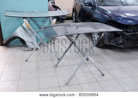Stand with details for body repair. Car windshield