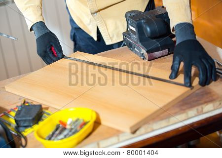 Close up of male hands measuring wood