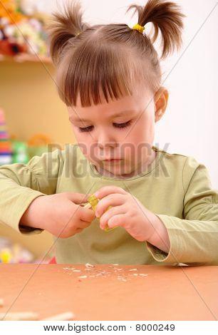 Little Girl Sharpening A Pencil