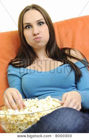 Young Woman Eat Popcorn On Orange Sofa