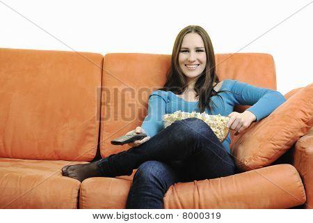 Junge Frau Essen Popcorn auf orange sofa