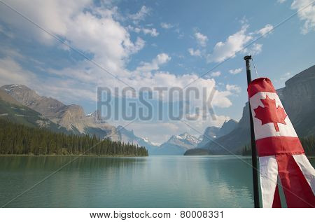 Canadian Landscape With Mountains, Maligne Lake And Flag. Alberta