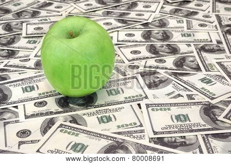 Green Apple On Heap Of Dollars