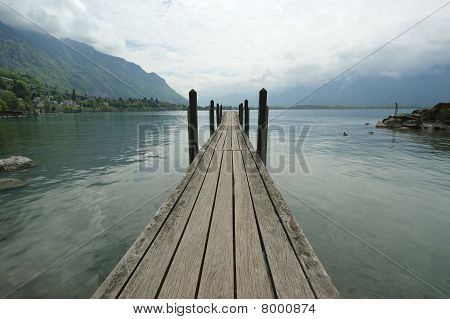 The Wooden Pier For Boats And Yachts On The Background Of The Lake Water And Overcast Skies