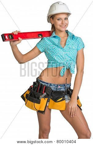 Beautiful girl in white helmet, shorts and shirt holding builder's level on the shoulder