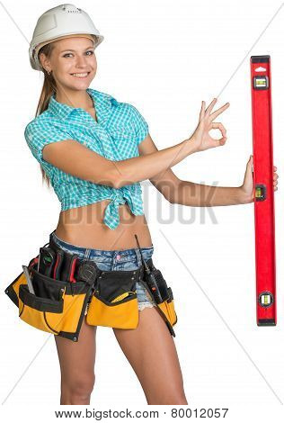 Beautiful girl in white helmet holding builder's level and showing OK hand sign