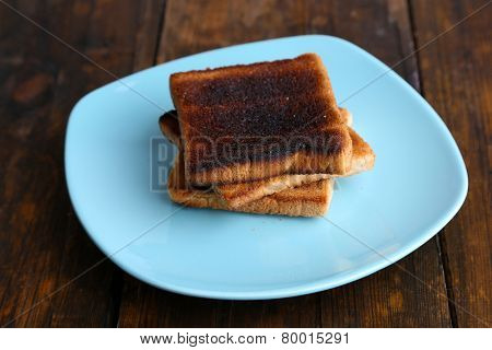 Burnt toast bread on turquoise plate, on wooden table background