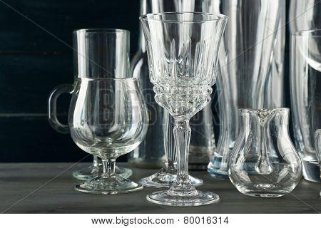 Different glassware on dark color wooden background
