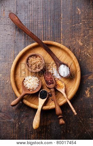 Different Types Of Food Coarse Salt In Wooden Spoons On Dark Background