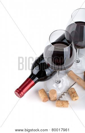 Red wine glasses, bottle and corks. Closeup. Isolated on white background