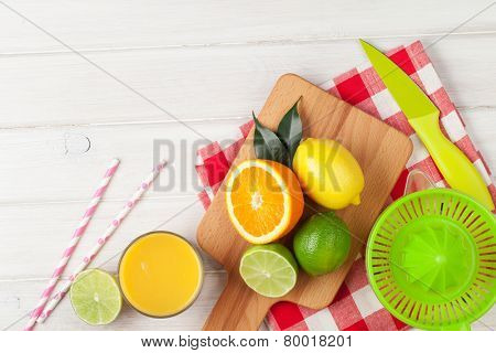Citrus fruits and glass of juice. Oranges, limes and lemons. Over white wood table background with copy space
