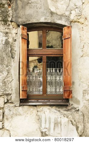 Wooden window with shutters in town.
