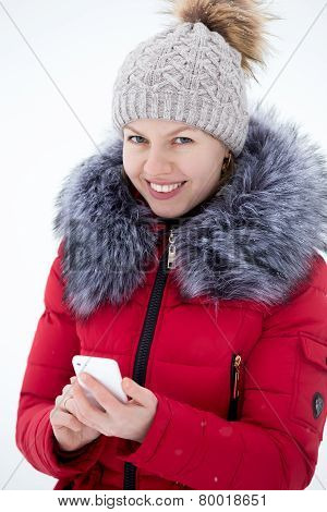 Happy Smiling Female In Red Winter Jacket Texting With Mobile Phone, Outdoors Against The Snow, Look