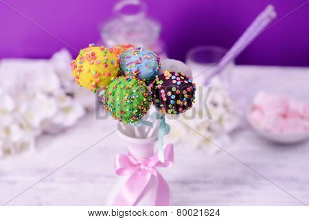 Sweet cake pops in vase on table on purple background