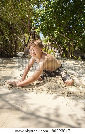 Happy Young Boy Is Digging In The Sand