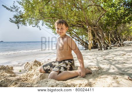 happy young boy is digging in the sand of the beach and constructing sand buildings