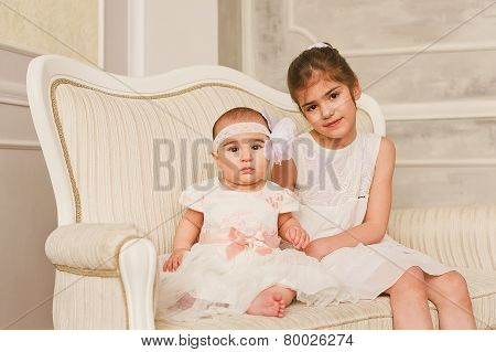 Little girl spending happy time with her infant sister