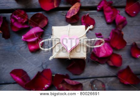 Giftbox with small decorative heart on its top and rose petals around