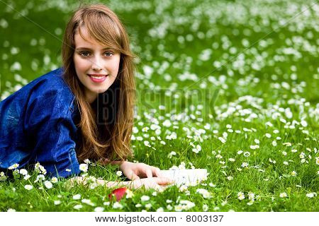 Girl lying on grass with book