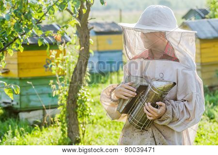 Teenage beekeeper and beehive on bee yard