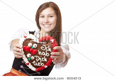 Young happy smiling woman in dirndl dress holding Oktoberfest gingerbread heart.