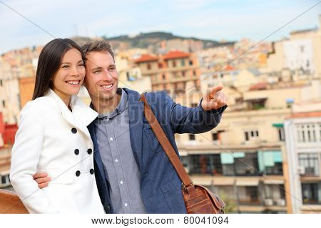 Romantic happy urban couple looking at view of Barcelona. Smiling lovers enjoying cityscape with famous landmarks. Stylish urban young man and woman on travel in Catalonia, Spain, Europe.