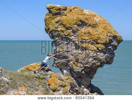 Man pushing a large rock into the abyss