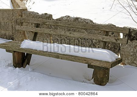 Old Wooden Bench Covered With Snow In Northern Italy