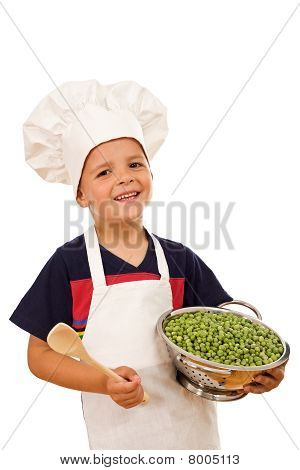 Niño feliz con gorro de cocinero y una taza de guisantes verdes