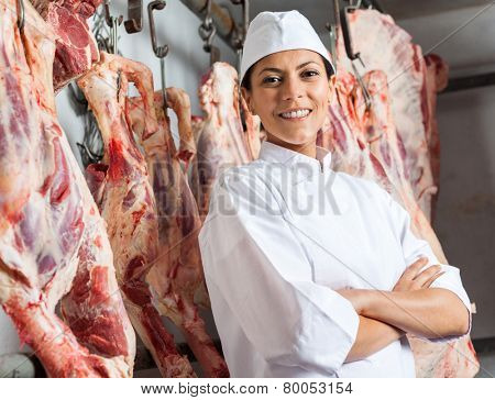 Portrait of happy mid adult female butcher standing arms crossed in slaughterhouse