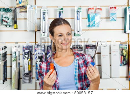 Beautiful customer comparing screwdrivers in hardware store