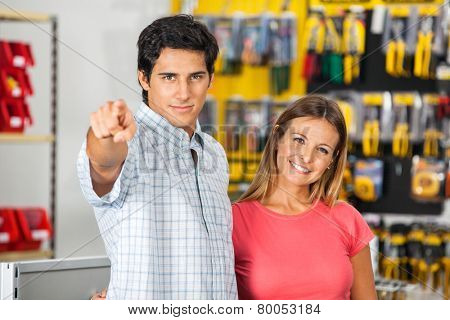 Portrait of confident woman with man pointing at you in hardware store