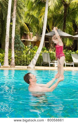 Active Father Teaching His Toddler Daughter To Swim In Pool On  Tropical Resort In Thailand, Phuket.