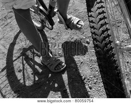 young bicyclist stopped to rest in black and white