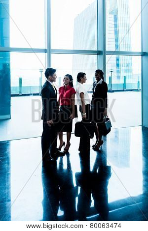 Group of business people standing in lobby or hall, a city skyline in the background