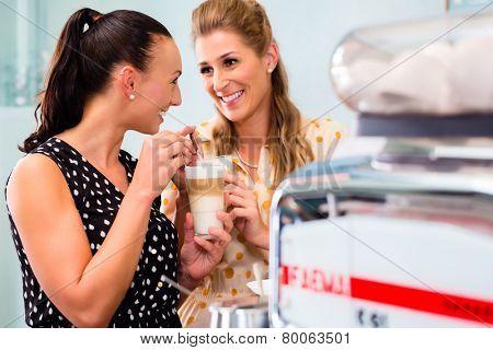 Two girls, best friends, drinking latte macchiato in cafe or coffee bar